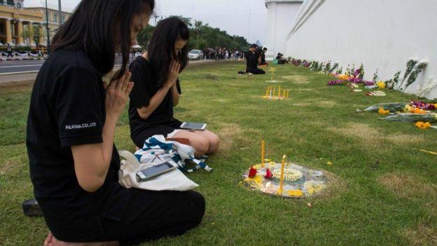 Mujeres llorando en Tailandia de luto por el rey fallecido