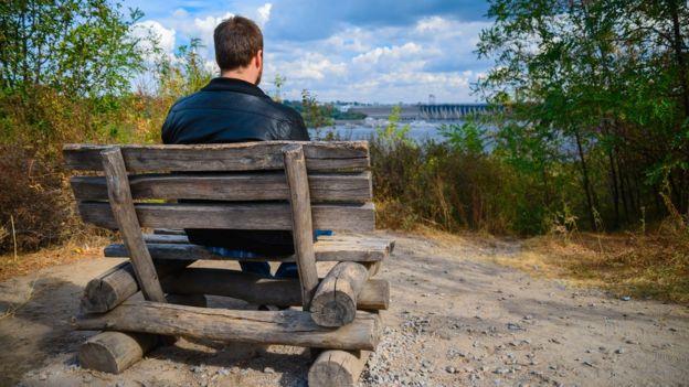 Un hombre sentado en un banco, visto de espaldas