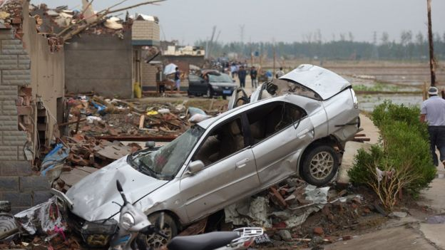 Residents walk in the rubble of destroyed houses after a tornado in Funing, in Yancheng, in China