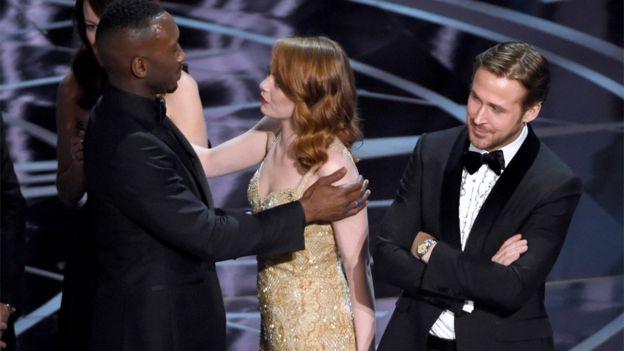 Mahershala Ali de Moonlight abraza a Emma Stone, que ganó el premio a la mejor actriz por La La Land, mientras su coestrella Ryan Gosling mira, confundido.