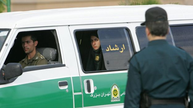A policewoman looks out of a van of Iran's morality police in Tehran in July 2007