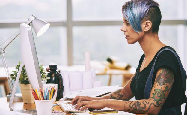 身上有刺青的女年輕在電腦前工作