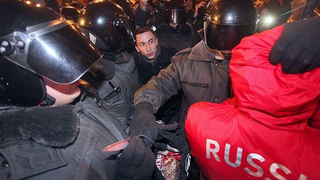 Policías rusos arrestando a un aficionado.