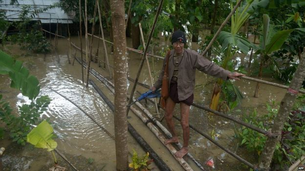 An elderly resident uses a rickety bamboo bridge over floodwaters to reach a house at Nyaung Don township in the Irrawaddy region on 5 August 2015