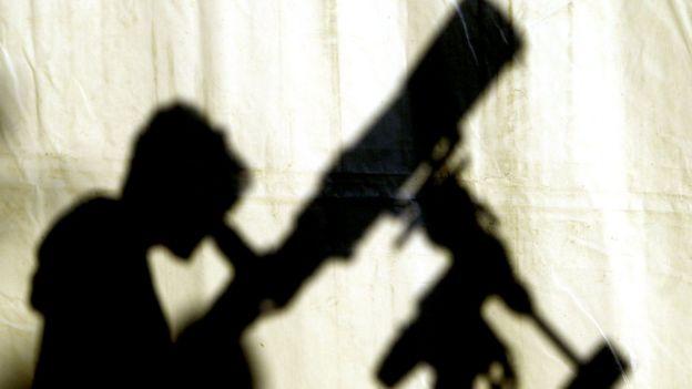 Sombra de un joven viendo telescopio