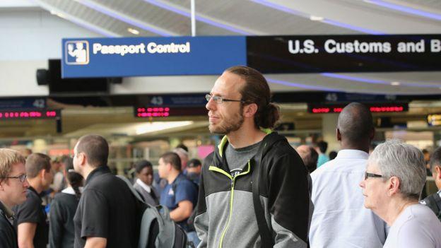 Personas en el control de migraciones en un aeropuerto en EE.UU.
