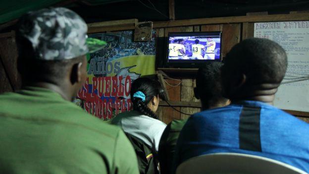 Guerrilleros miran un partido de fútbol