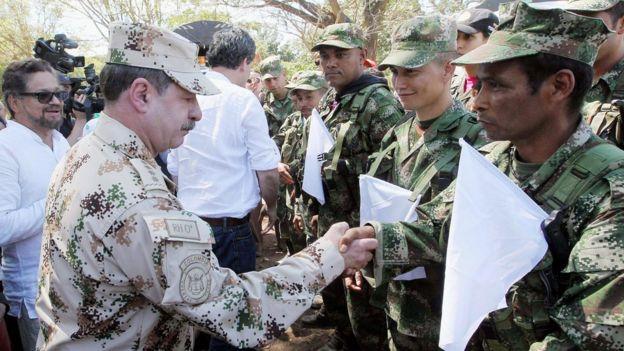 El comandante del ejército colombiano Javier Florez saluda a combatientes de las FARC que arribaron a una zona de transición.