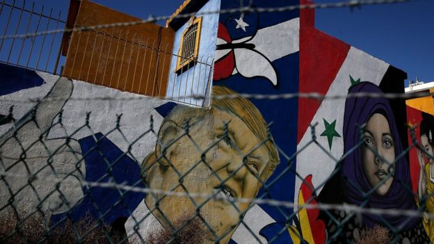 A mural of US President Donald Trump and a young girl in a headscarf in front of a Syrian flag is displayed on the side of a home on January 27, 2017 in Tijuana, Mexico