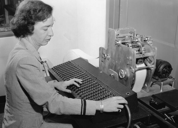 Lieutenant Grace Hopper uses a new calculating machine invented by Commander Howard H. Aiken for the Navy's use during WW1