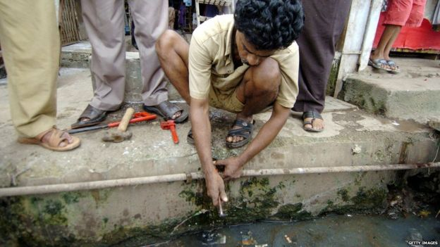 An Indian worker from the Brihanmumbai Muncipal Corporation (BMC) worker is watched by bystanders as he makes repairs on a drinking waterpipe that runs through sewage waste in a slum district in Mumbai