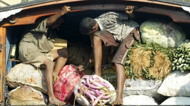 Two men ride on back of open truck, whilst holding in food produce for sale at market stall in Colombo. File photo
