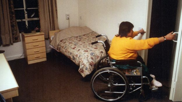 A woman pulling herself out her room in her wheelchair