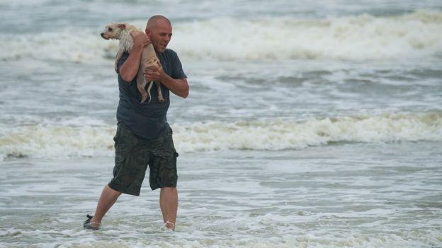 Hombre sujetando a su perro