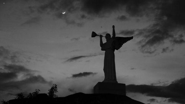 La estatua de un ángel en el cementerio, sobre el fondo del cielo nocturno.