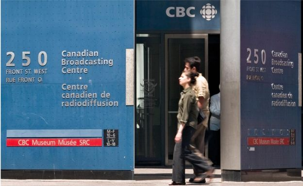Pedestrians walk in front of the Canadian Broadcasting Corporation (CBC) building in downtown Toronto