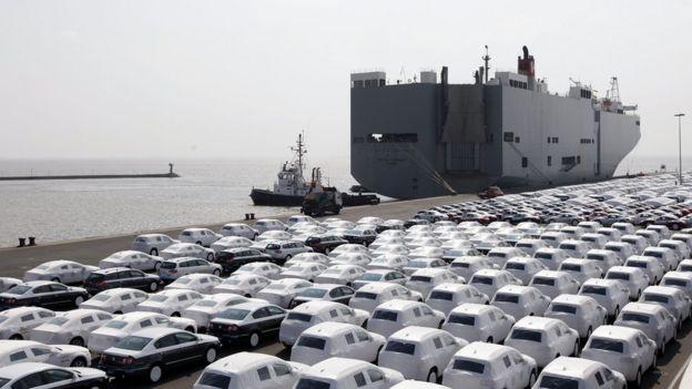 VW cars wait to get loaded onto transport ships at the Volkswagen car factory Emden