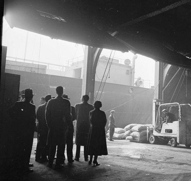 Grupo observa a estibadores del puerto de Nueva York en 1955.