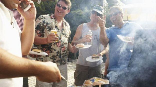 Hombres en una barbacoa comiendo hamburguesas y bebiendo cerveza y agua.