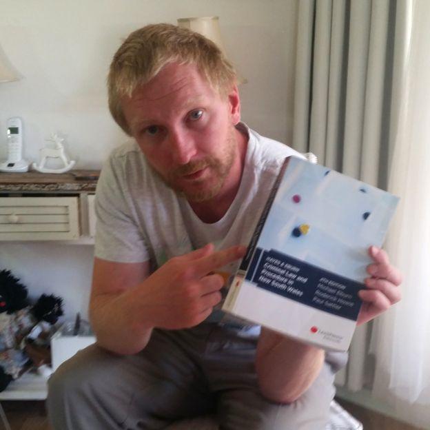 Luke Brett Moore con un libro de leyes