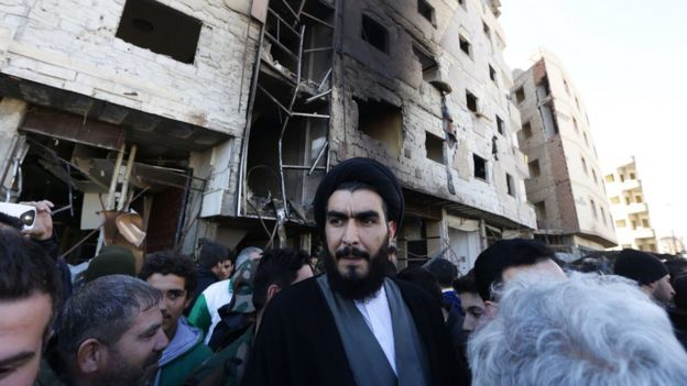 A Shia cleric stands amid Syrian pro-government forces and residents at the site of suicide bombings in the area of a revered Shia shrine in the town of Sayyida Zeinab, on the outskirts of the capital Damascus, on Sunday