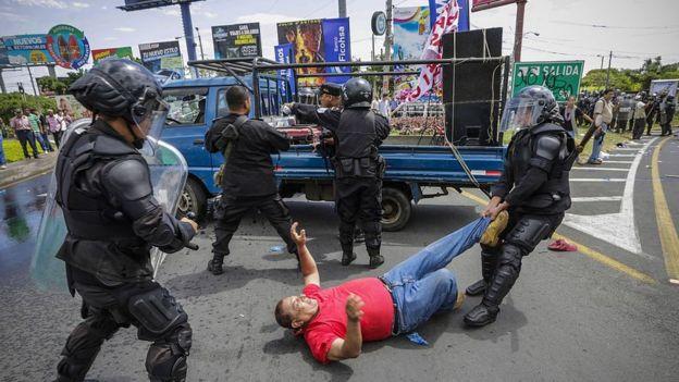 Policías nicaragüenses arrastran por el suelo a un hombre durante una protesta contra el Consejo Supremo Electoral.