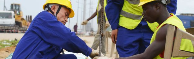 Chinese and Ivorian workers in Abidjan, Ivory Coast - July 2015