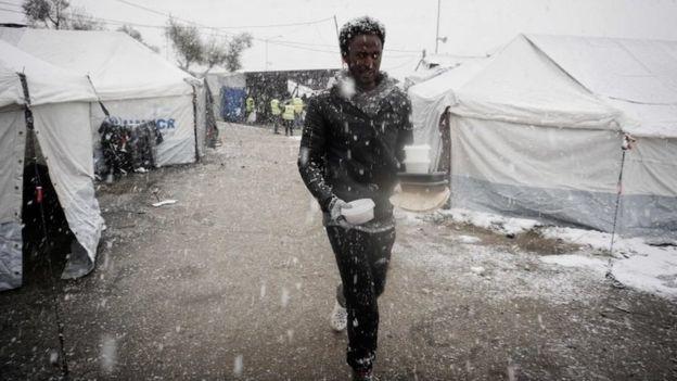 Un migrante camina tras recibir comida en un campamento en la isla griega de Lesbos, el nueve de enero de 2017.