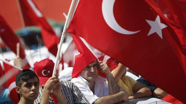 Miting alanında toplanan kalabalık ellerinde Türk bayraklarıyla bekliyor.