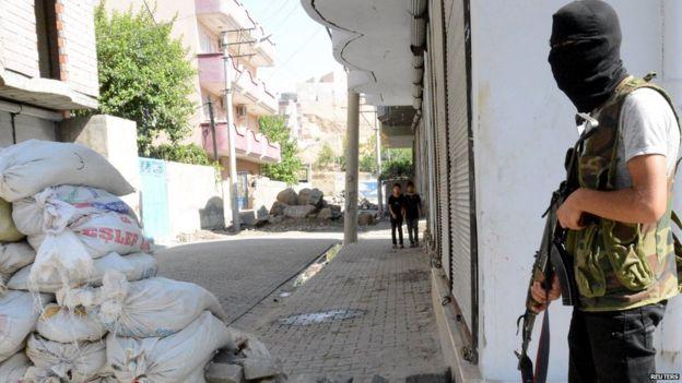 A Kurdish militant stands near a road blockade