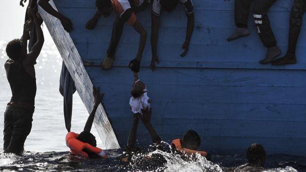 Un niño es trasladado desde el barco para llevarlo a los rescatistas