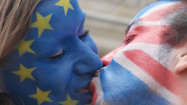 Una mujer con el rostro pintado con la bandera de la UE y un hombre con el suyo con la bandera de Reino Unido se besan