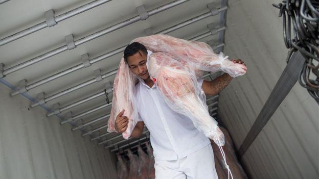 Homem carrega carne para frigorífico