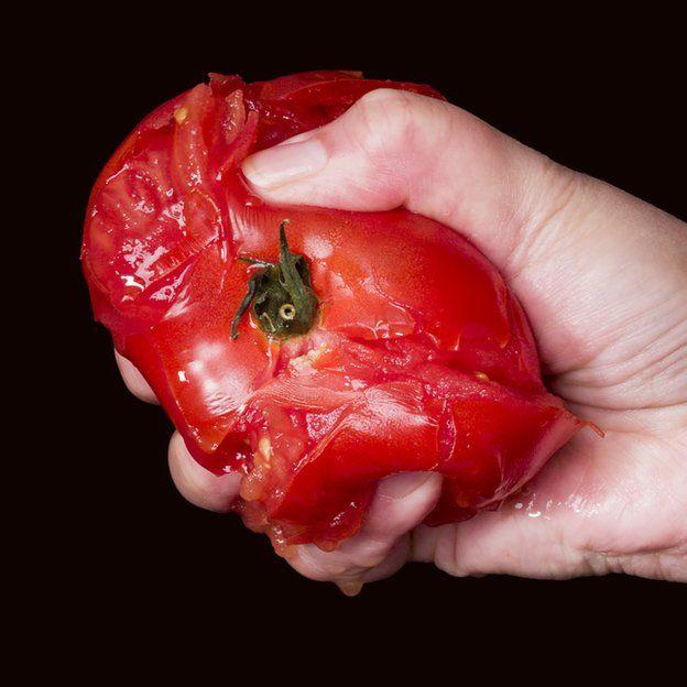 Mujer espichando un tomate