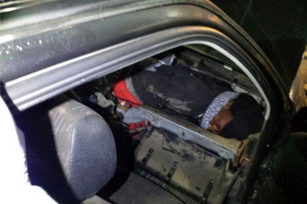 Inmigrante africano escondido en el tablero de un auto.