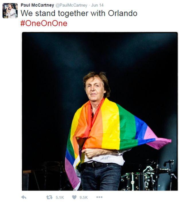 Paul McCartney envuelto en una bandera de arcoíris.