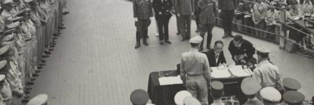 Japanese Foreign Minister Mamoru Shigemitsu (seated) signs the Japanese surrender document for emperor Hirohito aboard the USS Missouri