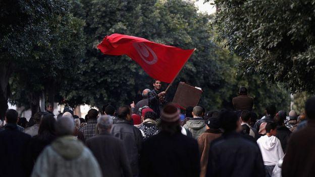 Tunisian man waves flad at demonstration