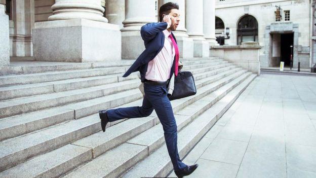 Un hombre corriendo escaleras abajo, mientras habla por un celular