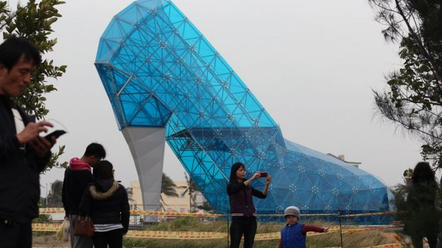 Tourists take pictures in front of a shoe-shaped church in southern Chiayi on 11 January, 2016