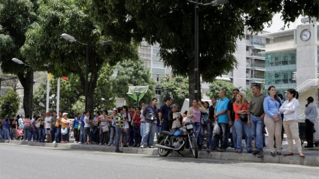 People queue to try to buy basic food items outside a supermarket in Caracas, Venezuela, April 28, 2016.