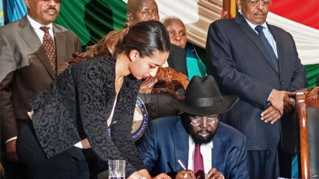 Salva Kiir signs the deal, as regional leaders look on