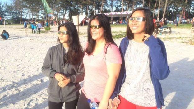 People watch the solar eclipse on Olivia beach, Belitung