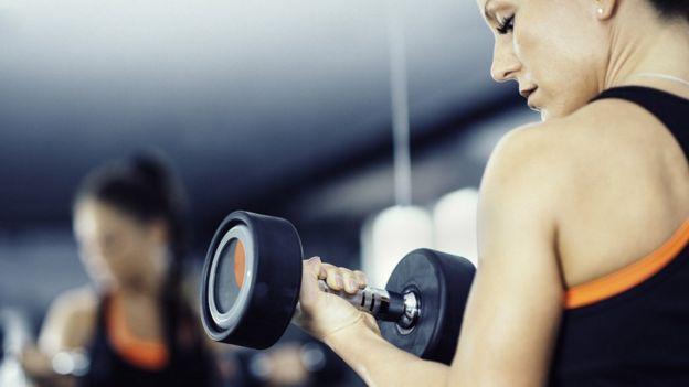 Una mujer levanta una pesa en el gimnasio