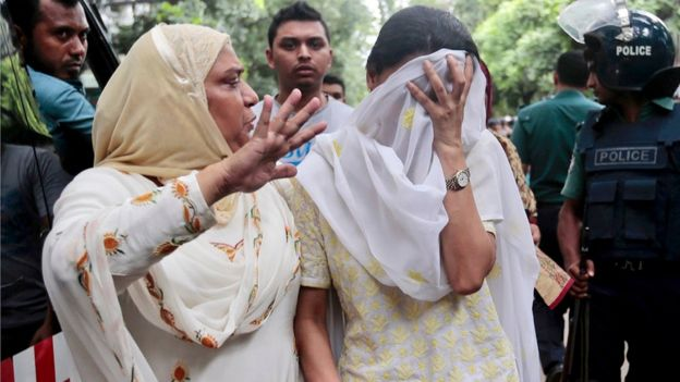 A relative tries to console Semin Rahman, covering face, whose son is missing after militants took hostages in a restaurant popular with foreigners in Dhaka, Bangladesh, Saturday, July 2, 2016