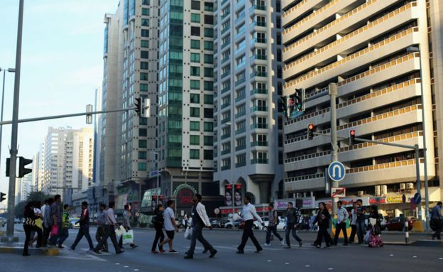 People walk across a main road in 2015 in Abu Dhabi, United Arab Emirates