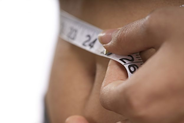 Close up of someone measuring waistline with a tape measure