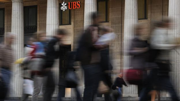 Commuters walk past the entrance of a branch of Switzerland's largest bank UBS in Lausanne
