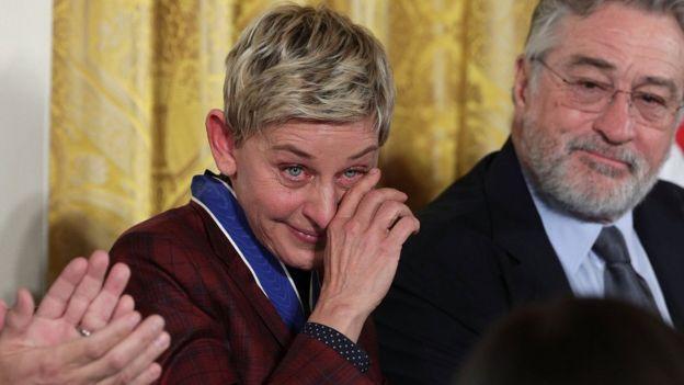 Comedian and talk show host Ellen DeGeneres wipes tears as actor Robert De Niro looks on
