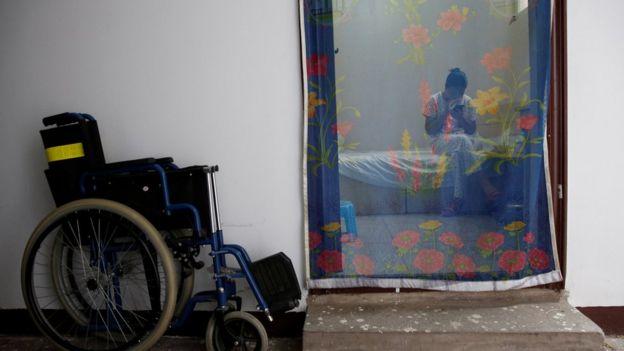 Mujer revisa su teléfono celular detrás de una cortina que hace las veces de puerta.